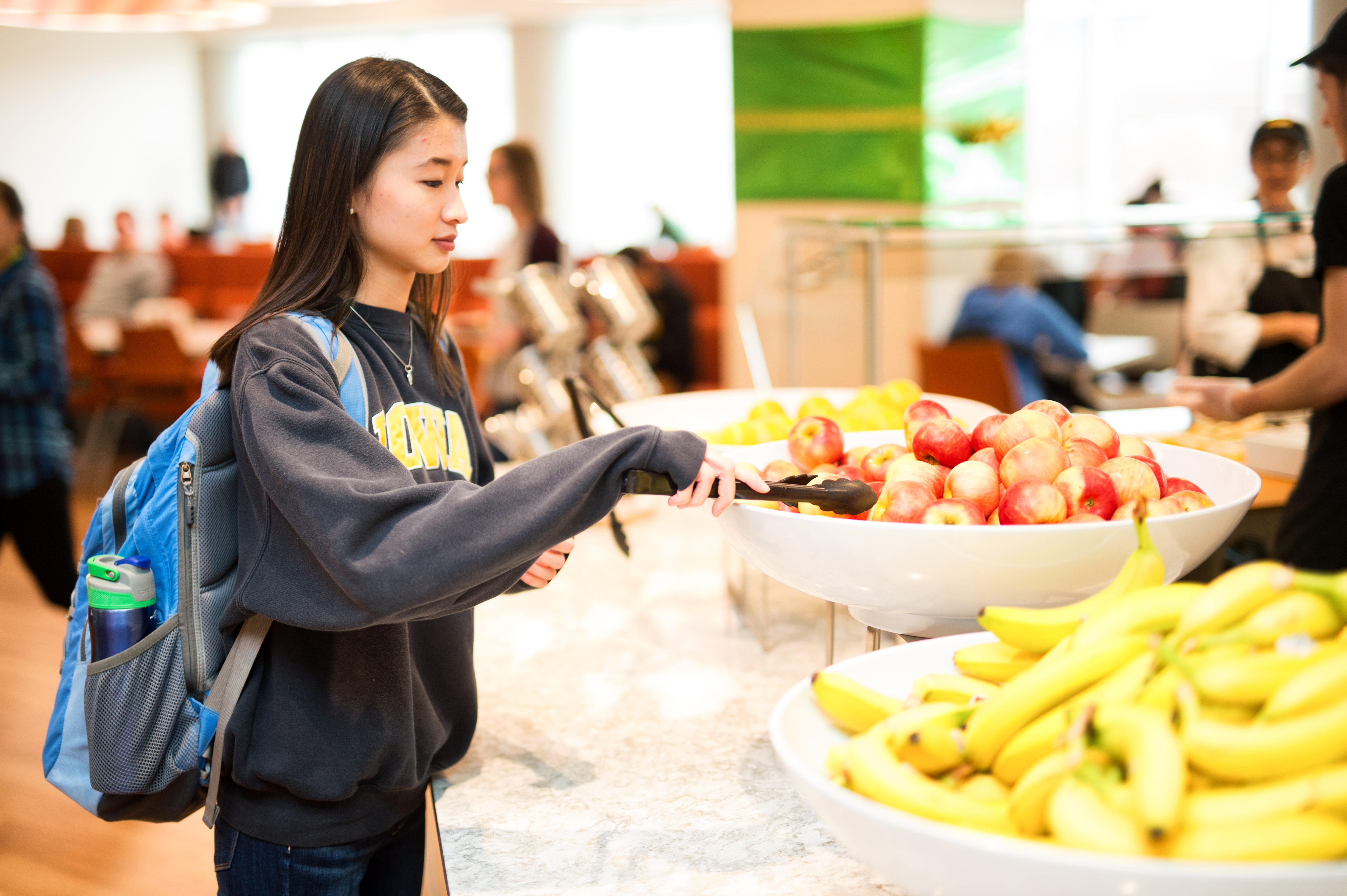 Student reaches for apple at Catlett Marketplace UIOWA