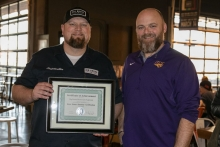 two men side by side, one holding Big Grove's Certificate of Achievement