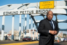 John Lewis against a picture of the Edmund Pettus Bridge in Selma