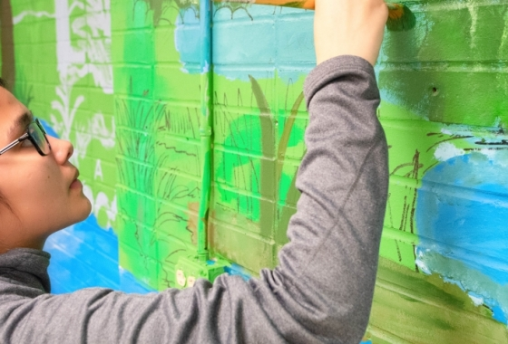 student painting sustainability mural