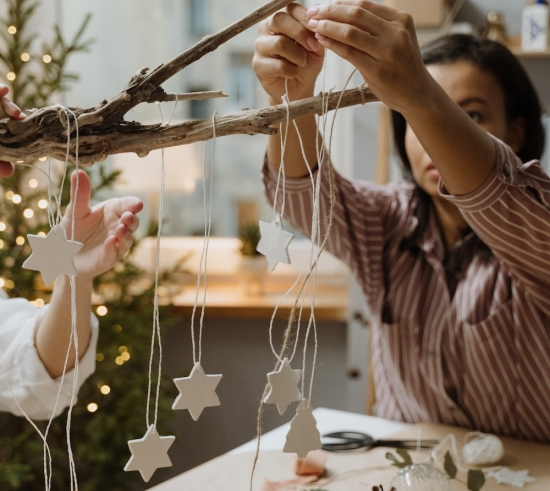 hanging white stars on strings from decorative branch